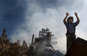 Un bombero llama a más rescatistas para que trabajen en la zona del colapso.