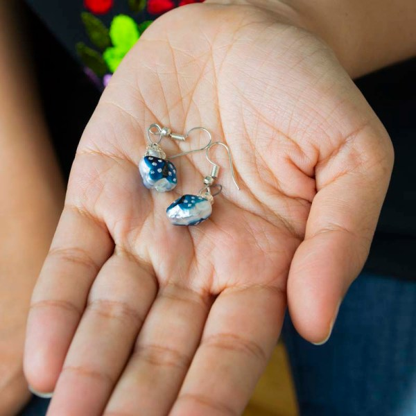 Handblown blue butterfly glass earrings shown on a hand.
