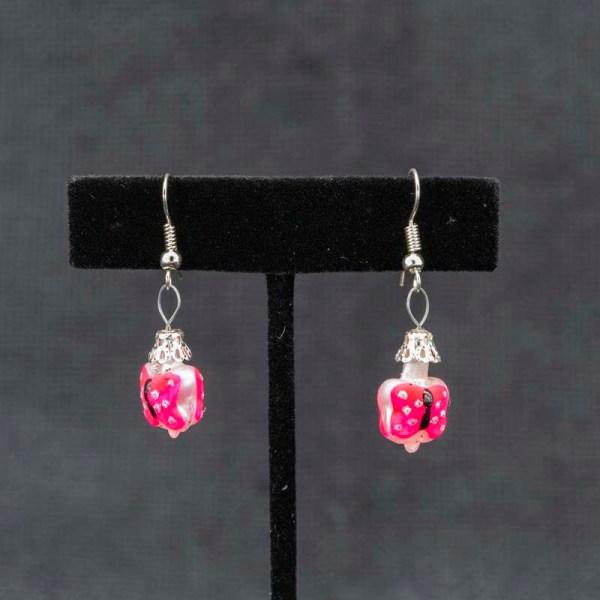 Handblown pink butterfly glass earrings shown hanging on a T earring display.