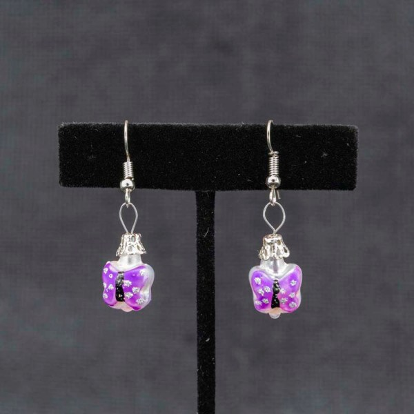 Handblown purple butterfly glass earrings shown hanging on a T earring display.