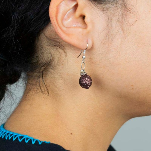 Woman wearing Christmas handblown glass earrings