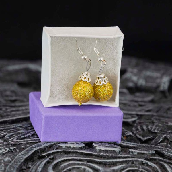Pair of handblown glass golden earrings shown in a box