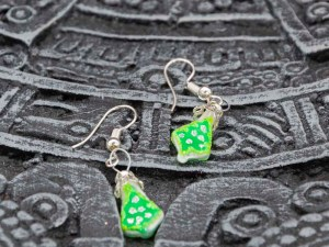 Christmas tree handblown glass green earrings shown on an Aztec calendar