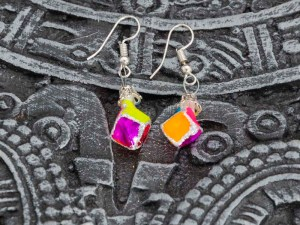 Pair of cube handblown glass pink earrings shown on a calendar Aztec