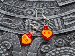 El Chapulin Colorado hand-blown glass red yellow earrings displayed on top of a Aztec calendar