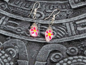 Cute little hand-blown glass earrings with pink flowers on top a n Aztec calendar