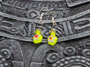 Cute little hand-blown glass yellow earrings with flowers on a Aztec calendar