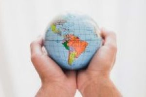 person-s-hand-holding-small-globe