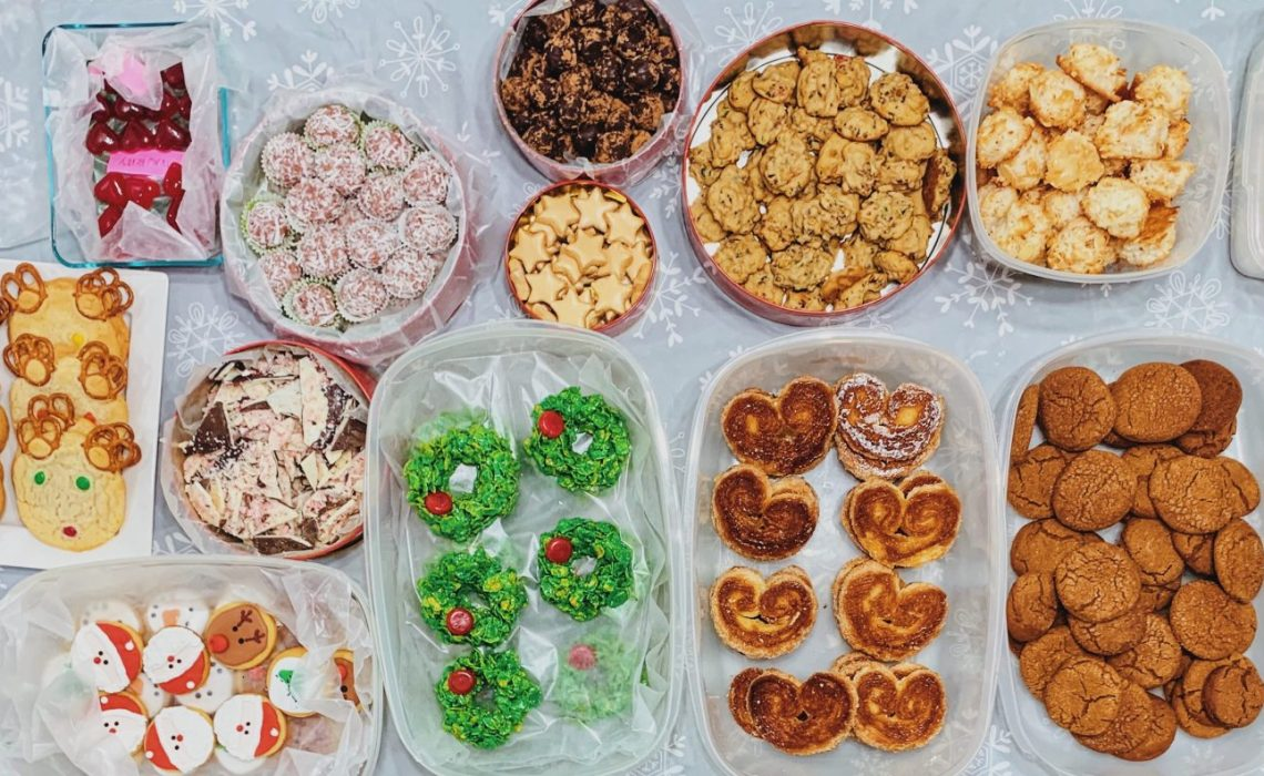 A table covered with snowflake tablecloth is filled with various Christmas cookies and treats.