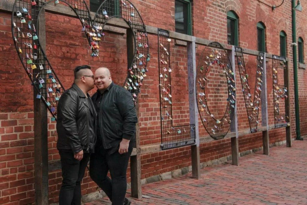 Mark and Pedro in front of a metal love sign