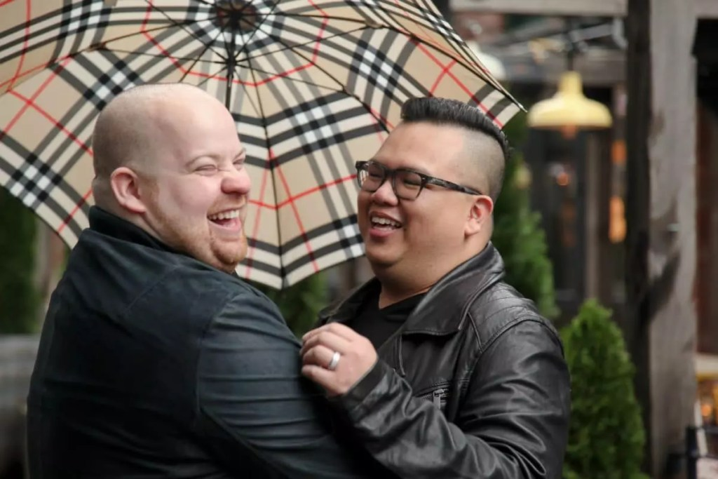 Mark and Pedro laughing under an umbrella