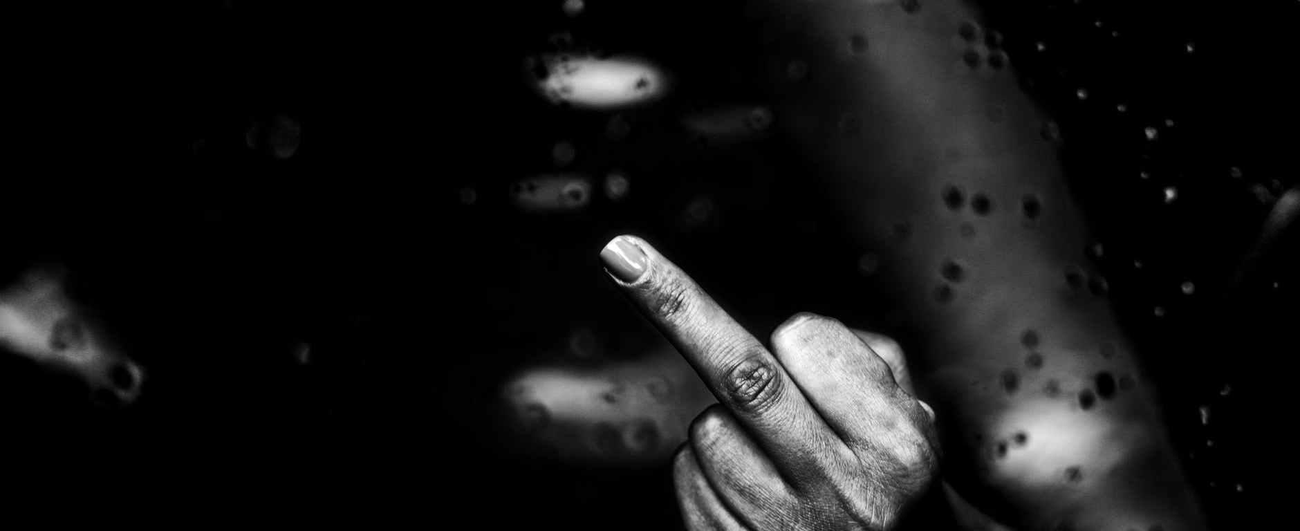 faceless black person demonstrating middle finger