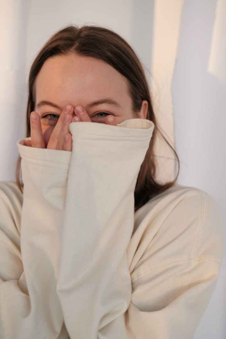 young woman laughing and covering face- laughter is happiness- A-Z of happiness