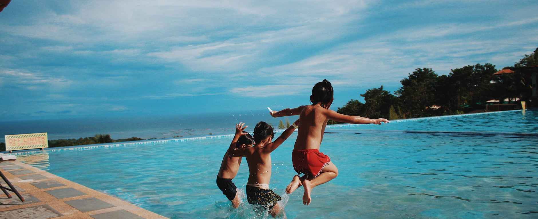 three boy s jumping into the water