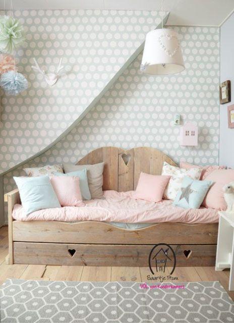 Divano letto in legno per la camera dei bambini con tessili dai toni delicati