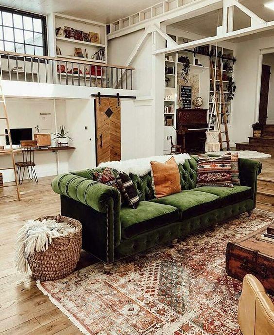 una casa industrial vintage con un bellissimo divano in velluto verde