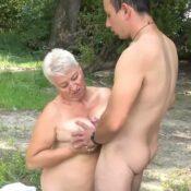 Rijpe vrouw met grote borsten heeft sex in de natuur