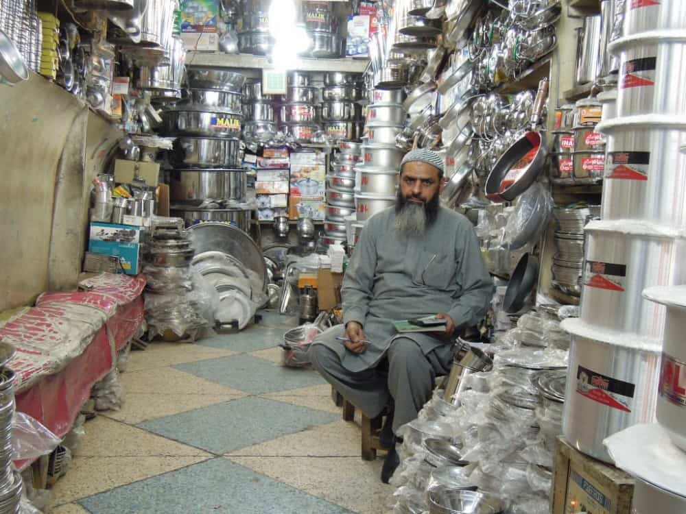 Shopkeeper sits in stall surrounded by stainless steel cookware and tableware