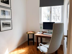 small study room with an antique desk by the window and lwarm light streaming through the tall window