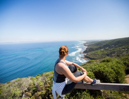 Me seating on a wooden railing of a lookout point that overlooks the bluest waters and wild beaches.