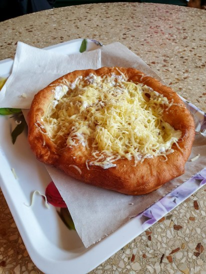 a perfectly round, perfectly golden langos with cream and cheese toppings.
