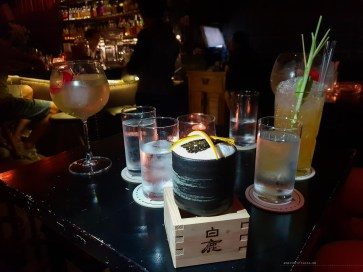 Creatively presented cocktail in the center of the photo - it's in a black porcelain cup inside a Japanese sake wooden box