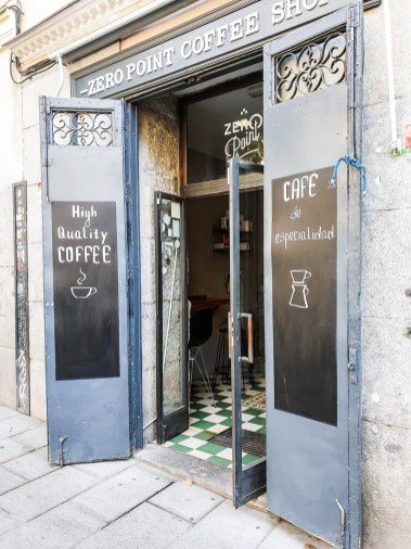 "The entrance to the Zero Point Coffee Shop with ""high quality coffee"" written on a chalkboard."