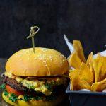 Ackee-smash-burger,-pumpkin-bun,-black-bean-patty,-ackee-chipotle-mayo-and-ackee-smash-served-with-homemade-green-plantain-chips