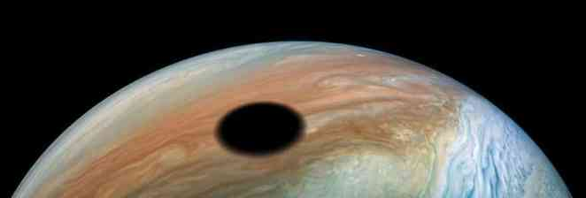 Jupiter's cloud tops one would witness a full solar eclipse as Io passes in front of the Sun.