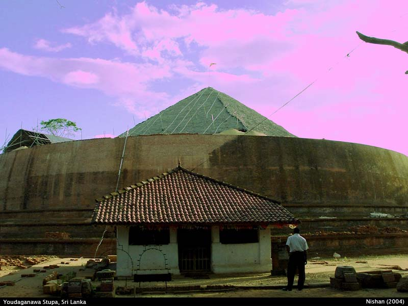 Yudaganawa Stupa under restoration with the image house used by the villagers is in front.