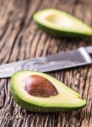 Avocado. Cut avocado on a oak wood background table. Selective focus.