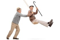 Two joyful senior gentlemen swinging on a swing and having fun i