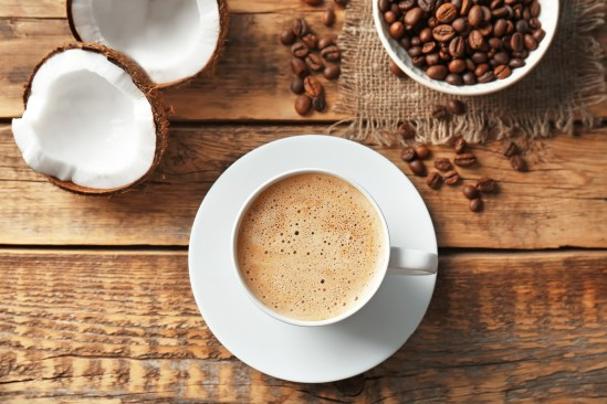 Cup of tasty coconut coffee and beans on wooden table