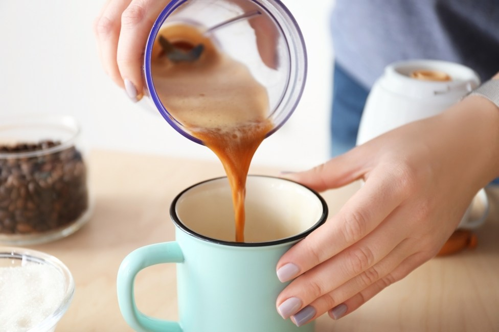 Woman pouring coffee with butter into mug, closeup