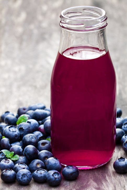 Blueberry juice in glass bottle on wooden table