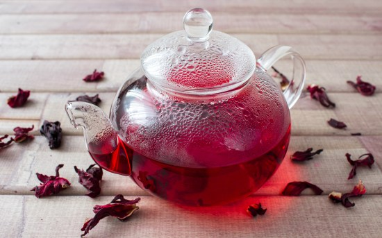 Hibiscus tea in glass teapot and dry flower on wooden background