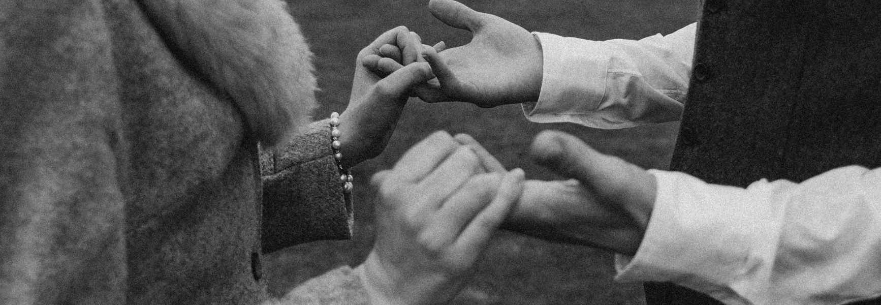monochrome photo of people holding hands