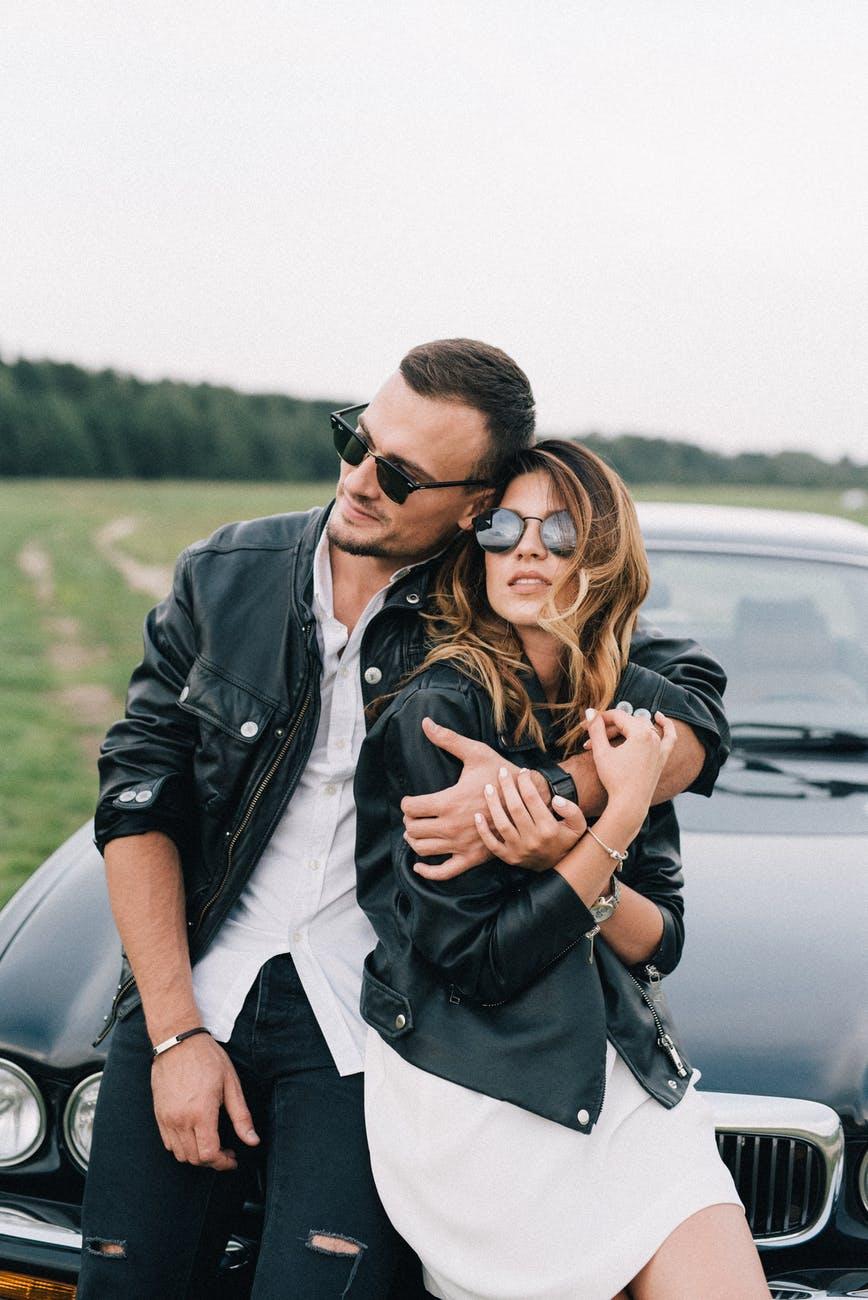 Ljubav u bolesti?  stylish couple in sunglasses embracing near luxury car in countryside