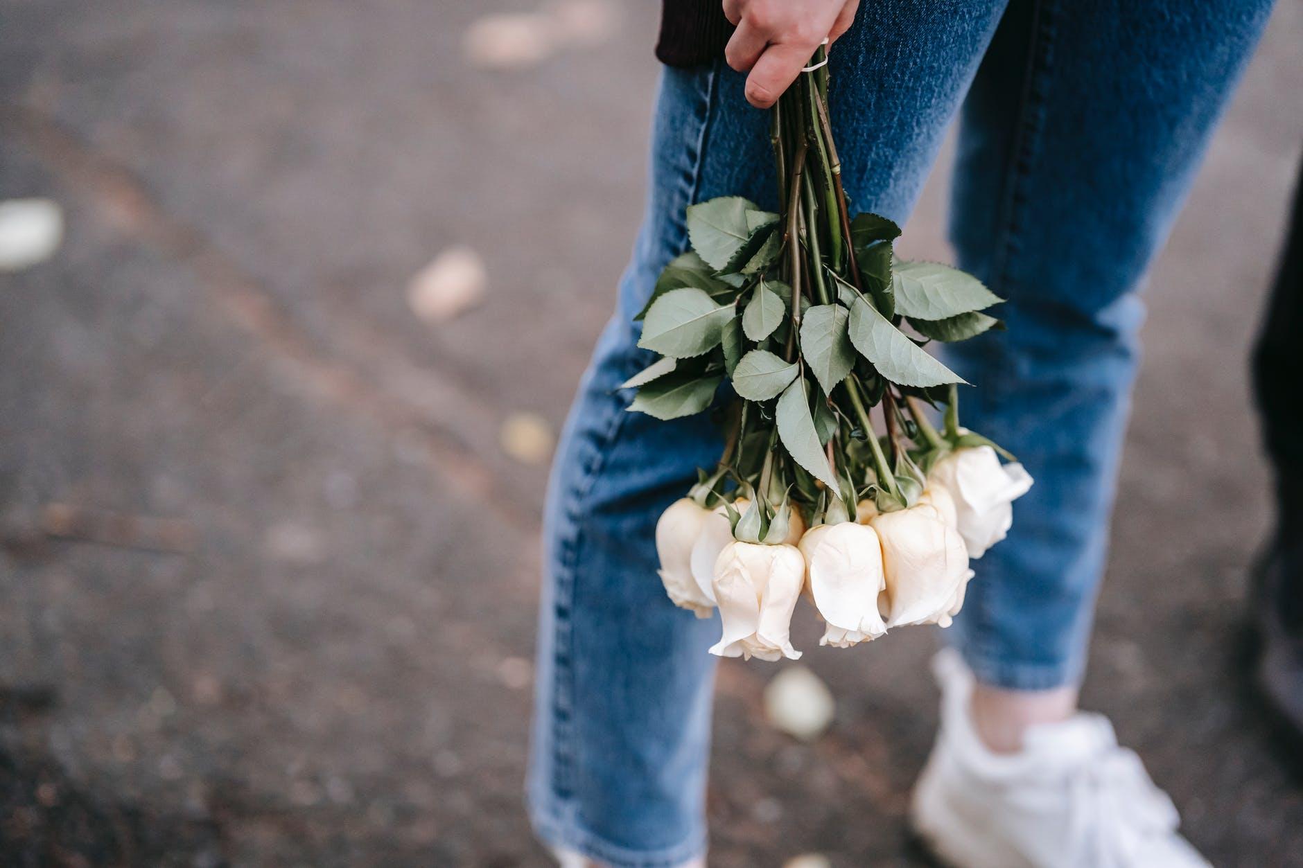 Za nekoliko znakova  woman in jeans with bouquet of fresh white roses