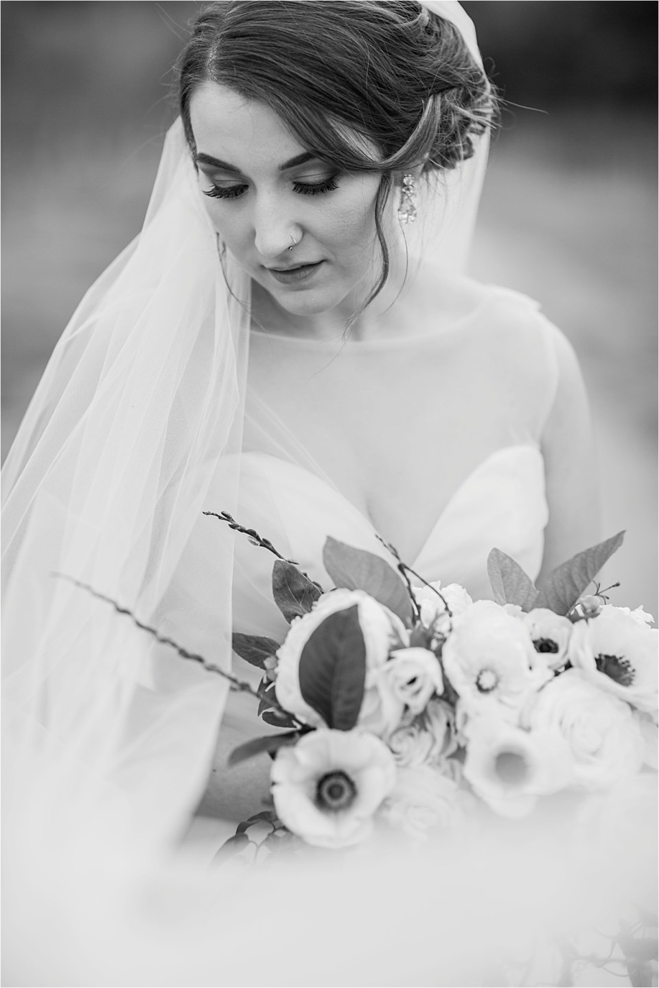 Bride shown in black and white gazing over her shoulder.