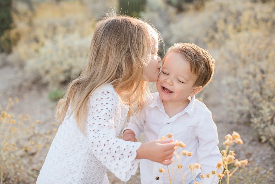 Big sister kissing baby brother in Honeybee Canyon in Tucson, Arizona