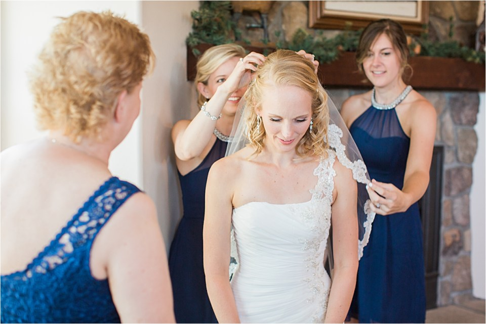 Bride getting veil on with her mother and sister.