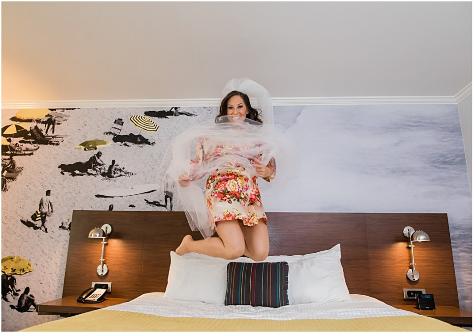 Bride jumping on the bed at Town and Country Hotel in San Diego.