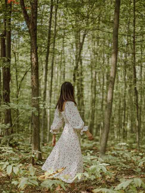 anonymous stylish woman strolling in green forest