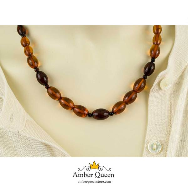 Cognac and Cherry Olive Amber Beads on Mannequin Close Up