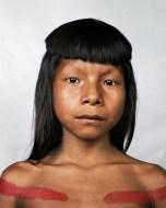 Ahkõhxet tem 8 anos e é membro da Kraho Tribe, que vive na bacia do rio Amazonas, Brasil. Existem apenas 1900 membros na tribo, que sobrevivem com comida cultivada num solo pouco fértil, usando ferramentas básicas. A pintura vermelha no seu peito é um dos vários rituais da tribo.