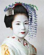 """Risa vive com 13 mulheres em Kyoto, no Japão, onde treina intensamente pra ser uma """"geisha"""". É a mais nova """"maiko"""" (jovem que já passou o teste pra treinar pra """"geixa"""") e tem 2 dias de descanso por mês. Tem 15 anos e deixou os pais em Tóquio."""