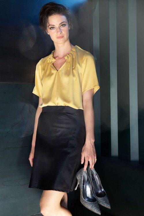 Her er blusen vist i strågul. Pumkin (orange), dueblå eller hvit bluse drapering i utrigning og kort erm Amuse by Veslemøy - 61182