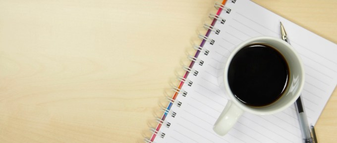 Image of coffee cup sitting on notepad