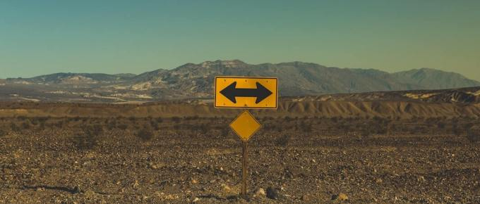 A yellow sign with arrows out in the dessert